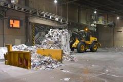 De wiellader vervoerden papierafval voor recycling in een molen - pa stock foto