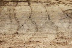 De wielsporen in de modder, detailvoetafdrukken asfalteren pers in de bouw op de stadionbouwwerf Stock Foto's