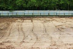 De wielsporen in de modder, detailvoetafdrukken asfalteren pers in de bouw op de stadionbouwwerf Royalty-vrije Stock Foto's