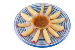 De wiggen van de appel met karamel dompelen op wit onder stock foto's
