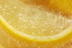 De Wiggen van de citroen in het Mineraalwater van het Glas Stock Fotografie