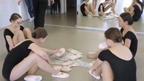 De wijfjes treffen voor les in modelschoolzitting voorbereidingen op de vloer stock footage