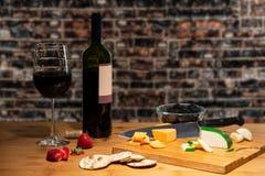 De wijn en een glas van kaas op een lijst met een knipsel vergezeld gaat schepen en bestek met fruit dat in stock afbeeldingen
