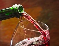 De wijn giet in het glas van de fles stock foto's