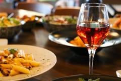 De wijn, nam toe, transparant in kristalglas met voorgerechten Onduidelijk beeldplaten met voedselachtergrond, close-up stock foto