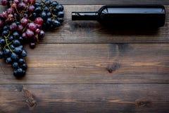 De wijnfles bundelt dichtbij van rode en zwarte druiven op donkere houten hoogste mening als achtergrond copyspace Royalty-vrije Stock Afbeelding
