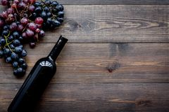 De wijnfles bundelt dichtbij van rode en zwarte druiven op donkere houten hoogste mening als achtergrond copyspace Royalty-vrije Stock Fotografie