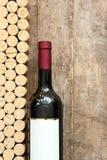 De wijnfles met kurkt tegen rustieke houten raad royalty-vrije stock foto