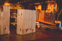 De wijnflessen in houten vakjes zijn op de lijst stock afbeeldingen