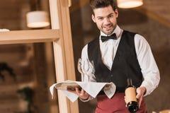 De wijnglazen en de fles van de kelnersholding Royalty-vrije Stock Afbeelding