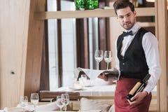 De wijnglazen en de fles van de kelnersholding Stock Foto