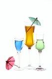 De wijnglazen worden gevuld met gekleurde dranken Stock Afbeelding