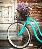 De wijnoogst bycycle met mand met lavendel bloeit dichtbij woode Stock Foto