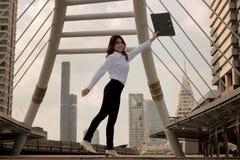 De wijnoogst stemde beeld van vrolijke jonge Aziatische bedrijfsvrouw die haar wapens met ringsbindmiddel opheffen bij stedelijke Royalty-vrije Stock Fotografie
