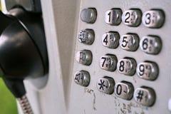 De wijzerplaat van de metaaltelefoon in de openbare telefooncel met zwarte letters en getallen op de zilveren geplateerde knopen Royalty-vrije Stock Foto