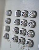 De wijzerplaat van de metaaltelefoon in de openbare telefooncel met zwarte letters en getallen op de zilveren geplateerde knopen Stock Foto