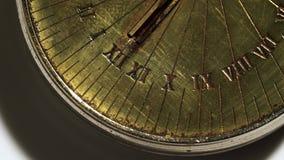 De wijzerplaat van een zonnehorloge roteert op een witte achtergrond Sluit omhoog stock footage