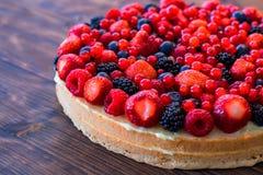 De wilde bessenmengeling met aardbeien, de frambozen, de braambessen, de bosbessen en redcurrants op een fruit koeken Royalty-vrije Stock Foto's
