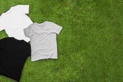 De willekeurig verspreide verschillende gekleurde T-shirts van mensen op grasachtergrond royalty-vrije stock foto's