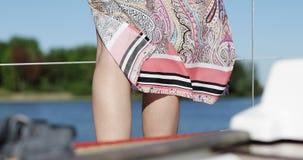 De wind blaast op de vrouwen` s heldere kleding Mooi benenmodel stock videobeelden
