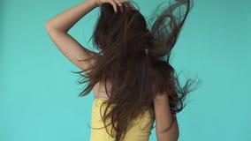 De wind blaast vrouwen` s haar terwijl zij in gele bovenkant op blauwe achtergrond danst stock videobeelden