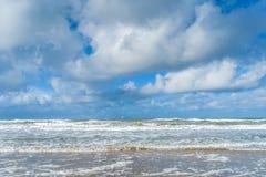 De wind en de golven leiden tot schuim op het strand royalty-vrije stock afbeelding