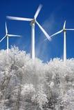 De wind maalt machtsgenerators tegen de winterbos Stock Foto's