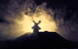 De windmolens is silhouet tegen de nachthemel Het nachtdecor met oude windmolen op heuvel met verschrikking stemde mistige achter vector illustratie