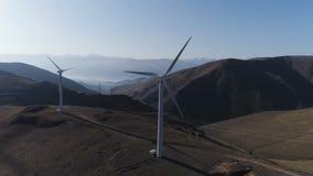 De windturbines leiden duurzame energie tot Koeltoren van elektrische centrale op achtergrond stock video