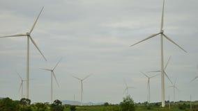 De windturbines op het groene gebied roteren met bewolking stock videobeelden