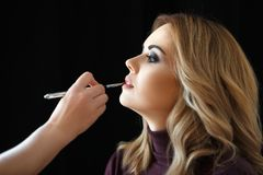 De winkel van de schoonheid Maak omhoog De hand van stilist schildert lippen met een borstel aan cli?nt royalty-vrije stock afbeelding