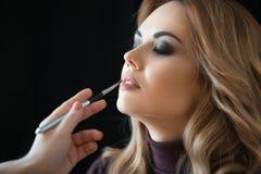 De winkel van de schoonheid Maak omhoog De hand van stilist schildert lippen met een borstel aan cli?nt stock afbeeldingen