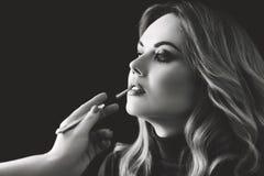 De winkel van de schoonheid Maak omhoog De hand van stilist schildert lippen met een borstel aan cli?nt De Zwart-witte foto van P royalty-vrije stock foto's