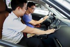 De winkelbediende die van AR met potentiële Chinese merk automobiele koper bij Dongguan-autotentoonstelling spreken Stock Afbeeldingen
