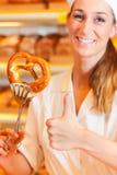 De winkelbediende pakt brood in bakkerij in Stock Foto
