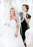 De winkelmedewerker zet huwelijkssluier op het hoofd van de bruid Royalty-vrije Stock Fotografie