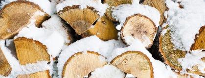 De winter achtergrondtextuurpatroon met gestapelde droge gehakte die brandhoutlogboeken met sneeuw worden behandeld Royalty-vrije Stock Fotografie