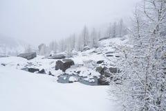 de winter alpien landschap met een bergstroom die over rotsen borrelen stock afbeelding