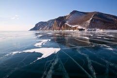 De winter Baikal met duidelijk ijs en bezinning van rotsen Stock Afbeelding