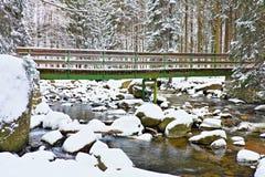 De winter bij rivier en oude voetgangersbrug Grote die stenen in stroom met verse poedersneeuw en lui water met low level wordt b Stock Afbeeldingen
