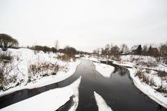 De winter daglandschap met rivier, sneeuw, hemel en bomen Stock Foto's