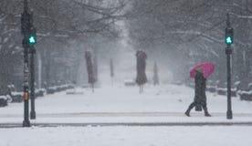 De winter in de Stad van Berlijn met lopende Mensen op de Straat en de Sneeuwval royalty-vrije stock foto's