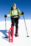 De winter die in de bergen op sneeuwschoenen met een rugzak en een tent wandelen Stock Foto