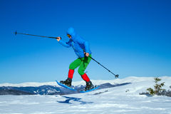 De winter die in de bergen op sneeuwschoenen met een rugzak en een tent wandelen Royalty-vrije Stock Afbeelding