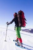 De winter die in de bergen op sneeuwschoenen met een rugzak en een tent wandelen Stock Afbeeldingen
