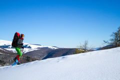 De winter die in de bergen op sneeuwschoenen met een rugzak en een tent wandelen Stock Fotografie