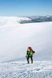 De winter die in de bergen op sneeuwschoenen met een rugzak en een tent wandelen Royalty-vrije Stock Foto
