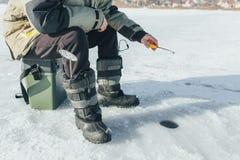 De winter die, hengeltribunes op het gat die op de vissen wachten vissen stock fotografie