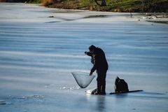 De winter die op het meer vist Mens die op ijs vissen stock fotografie