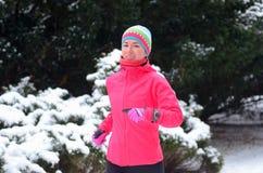 De winter die in park lopen: de gelukkige jogging van de vrouwenagent in sneeuw, openluchtsport Stock Foto